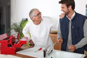 Plumber repairing sink for elderly lady